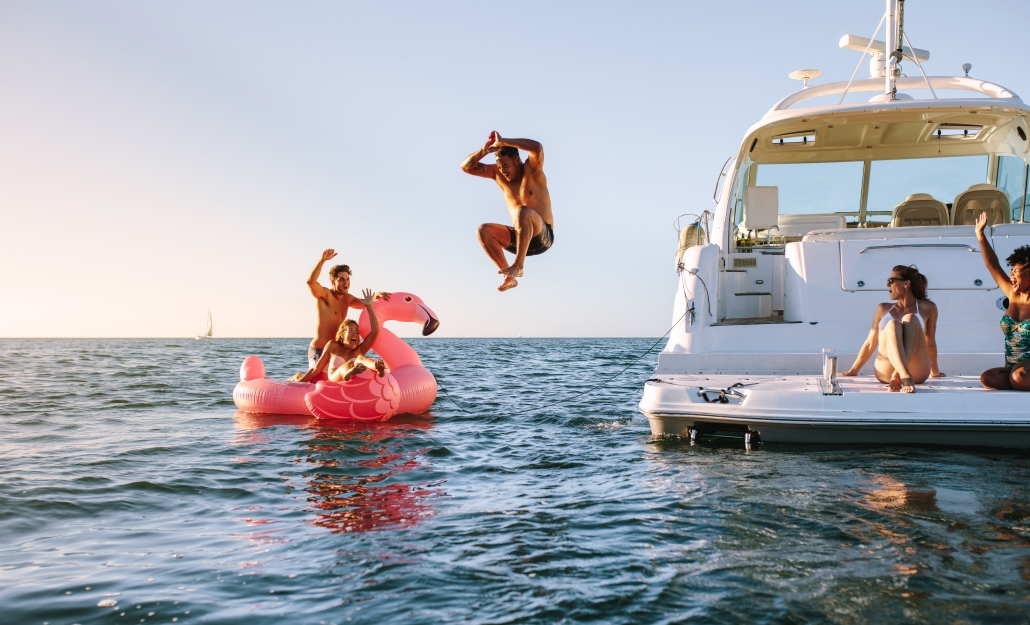 Man jumping off yacht next to couple in pink flamingo float